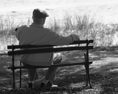 Elderly Man with a Hat Sitting on Bench